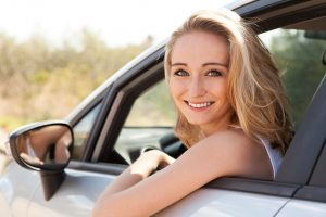 young attractive happy woman sitting in car summer portrait outdoor